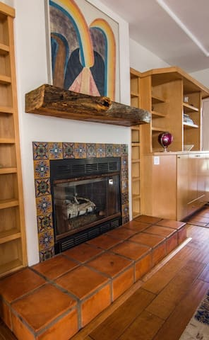 Working gas powered fireplace with Carol Summers painting above the mantle piece and bookshelves beyond. Niche lighting.