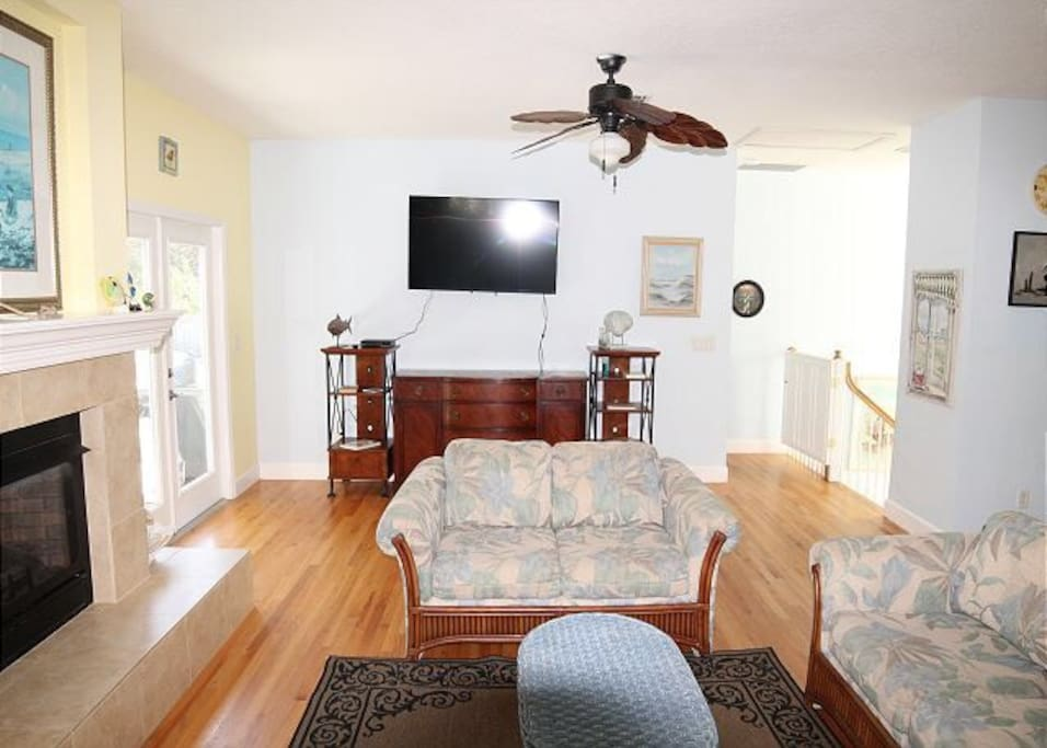 """Another view of the spacious living room with stairs to right leading down to second floor and front door.  """"Note"""" there is a baby gate or secured gate at top of stairs for children's safety or for your pets."""