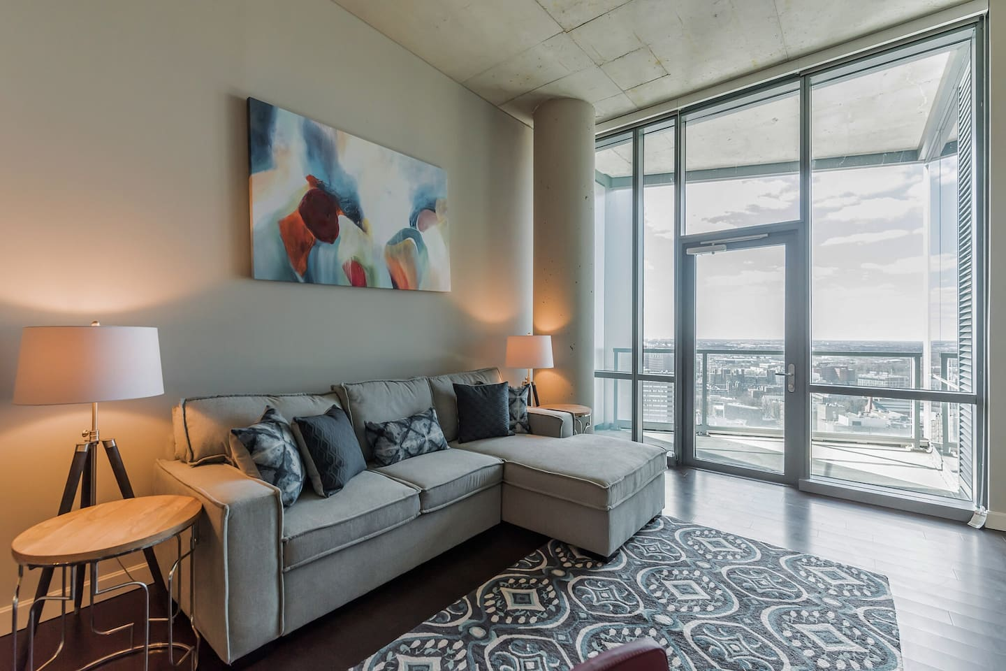 "Bright living area features a sleeper sofa for additional guests, a balcony, hardwood floors, and a 50"" Smart TV"