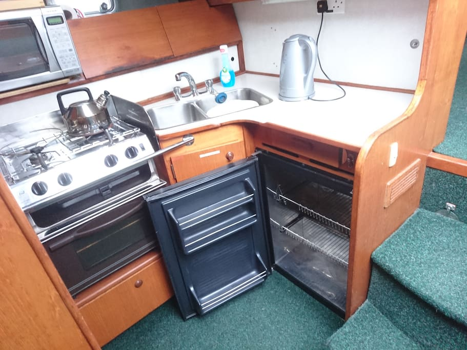 Galley with fridge, gas hob, microwave and kettle. Tea, coffee, sugar, washing up liquid and tea towel provided