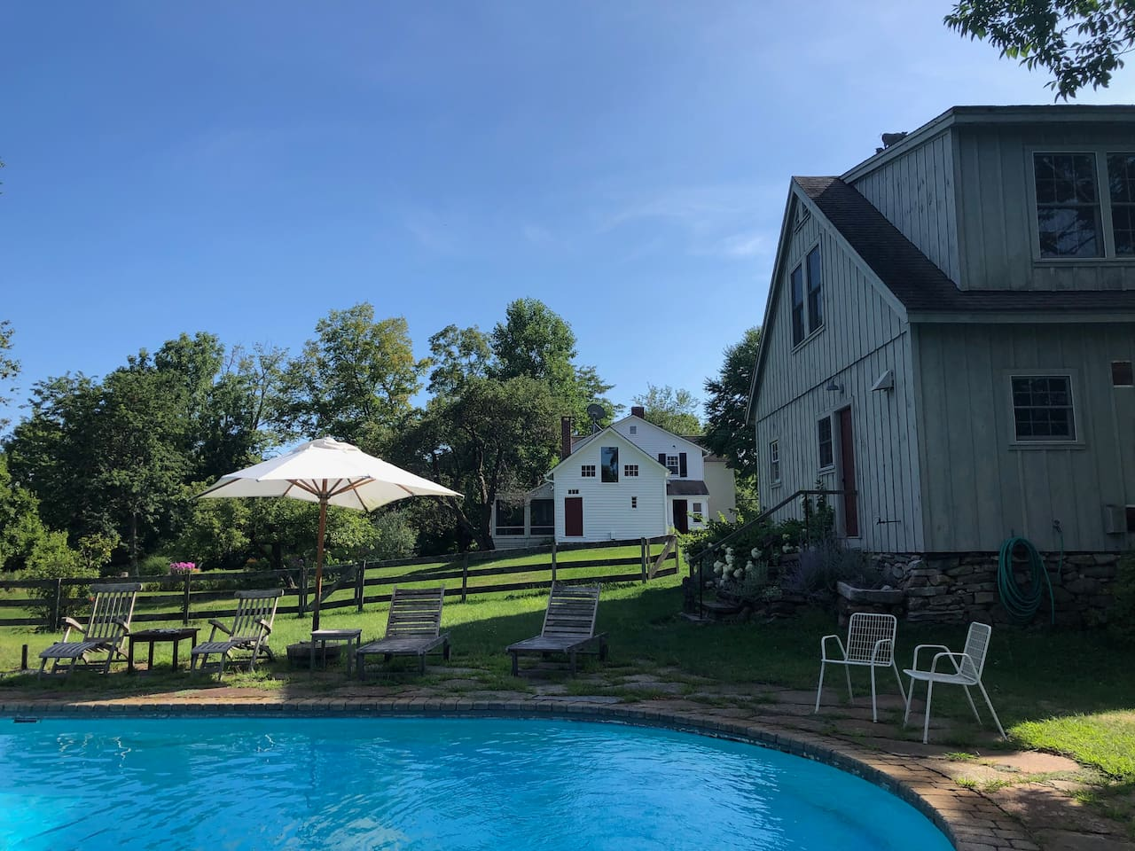 Grey Barn Guesthouse with pool. Farmhouse in the background.