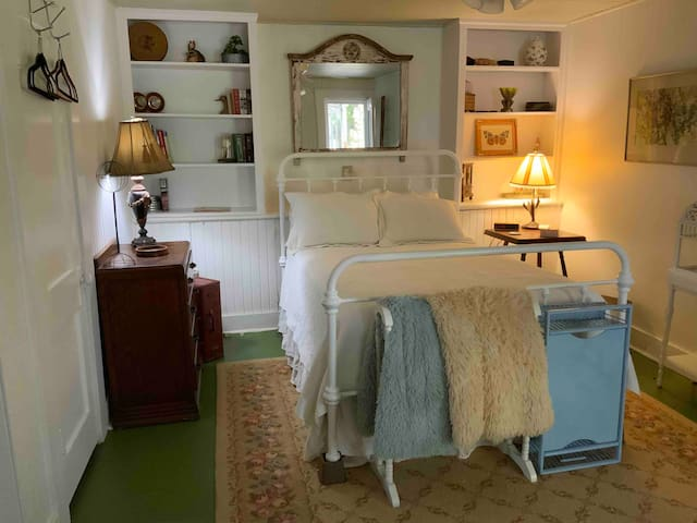 A spacious bedroom with a full size bed and comfy bedding.
