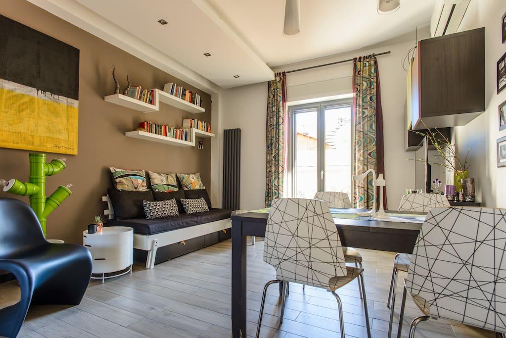Zona living: particolare del divano letto matrimoniale e del tavolo allungabile.