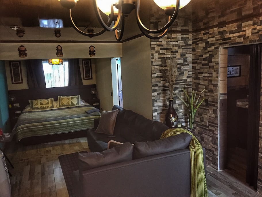 """King size bed along with the living room and a comfortable couch. The 59"""" TV can be moved to several positions, so you can see TV from the bed, couch or kitchen."""