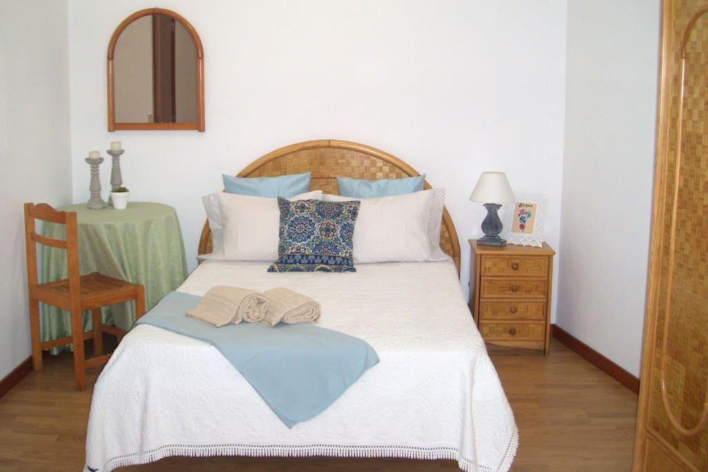 Quarto com 1 cama de casal e 2 de solteiro, com janela para o interior do prédio.