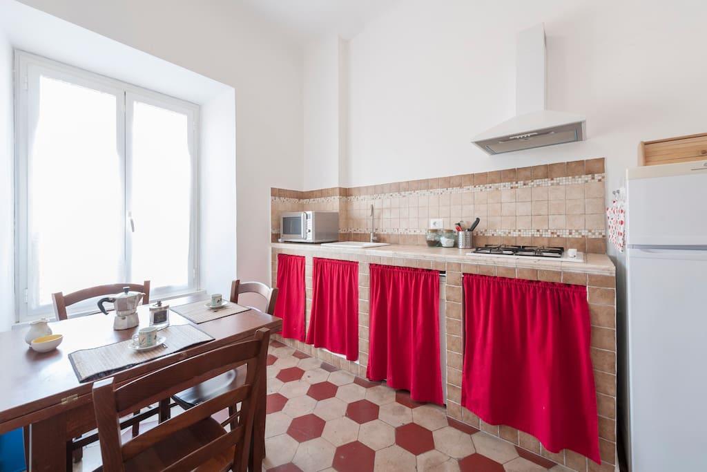 cucina in muratura, tavolo e sedie alla luce competa del giorno