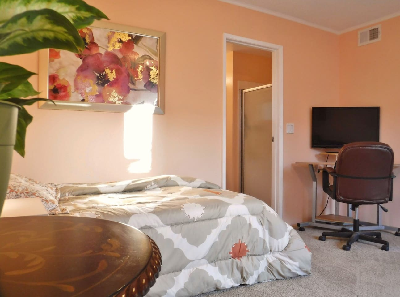 Tempurpedic queen size bed and the office space with a desk and a comfortable chair.