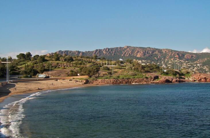 La jolie plage  de sable avec ses rochers plats à l'entrée du domaine.