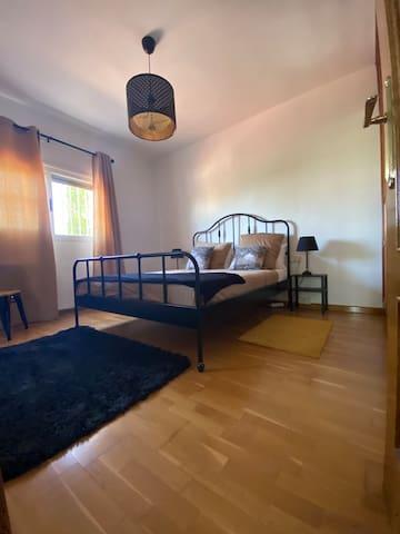 Chambre noire avec un lit 160x200, une belle mirroir au bout du lit et une très grande armoire