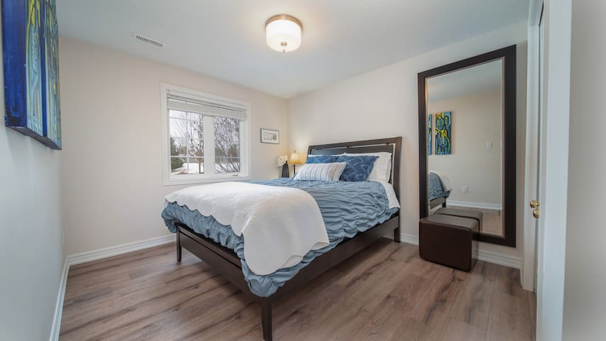 Crisp linens and a cozy duvet for a peaceful sleep in a queen-size bed...this is the south bedroom. Smaller bedroom, but with a big view of the garden and the majestic trees lining the fenced-off ravine and creek.