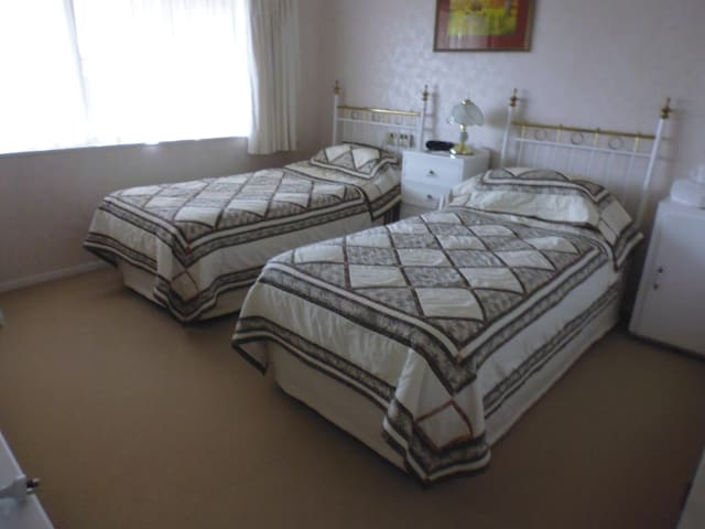 Two single beds, with a sink in the room