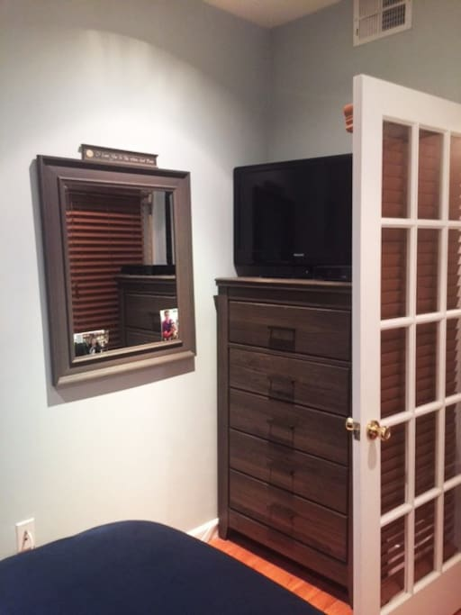 Dresser, mirror and television at the foot of the bed