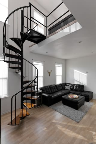 Living room with large L shaped section couch, ottoman, beer/wine fridge and spiral staircase.