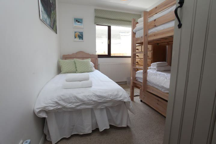 The second bedroom with a single bed and bunk beds. (Please note: the bunk beds can only be used by children under 10)
