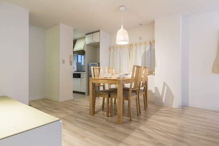 Dining table in the living space leading into the kitchen