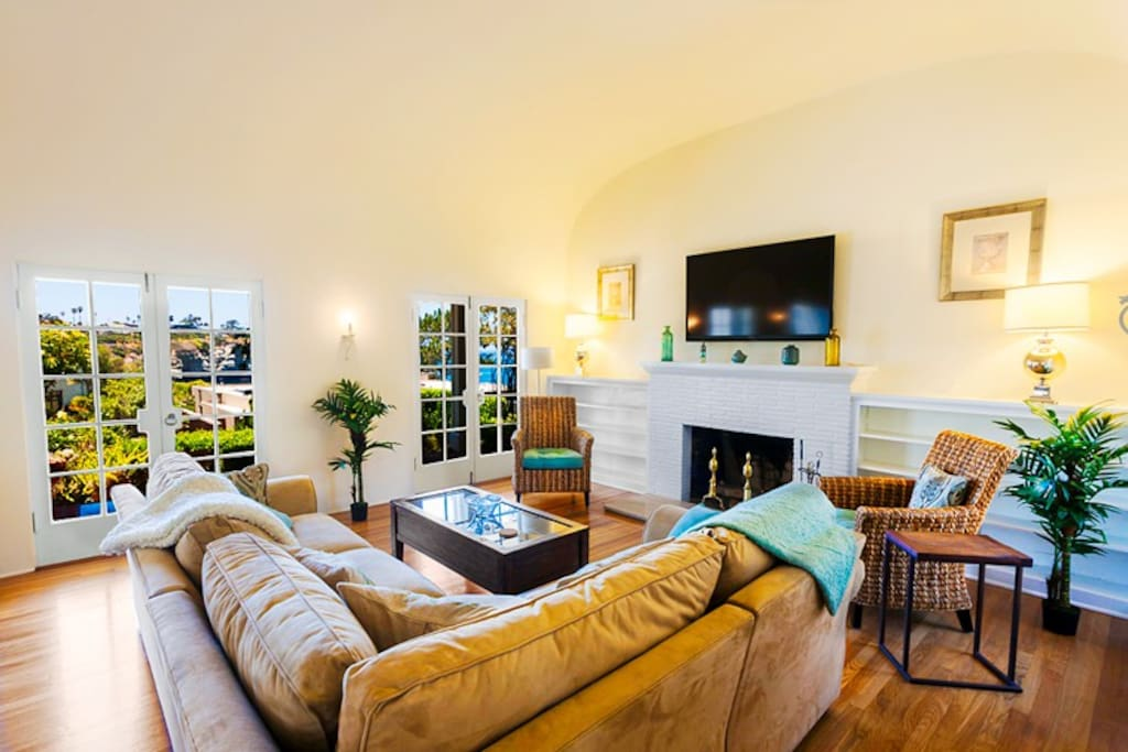 Spacious living room has 60 inch flat screen TV and fireplace.