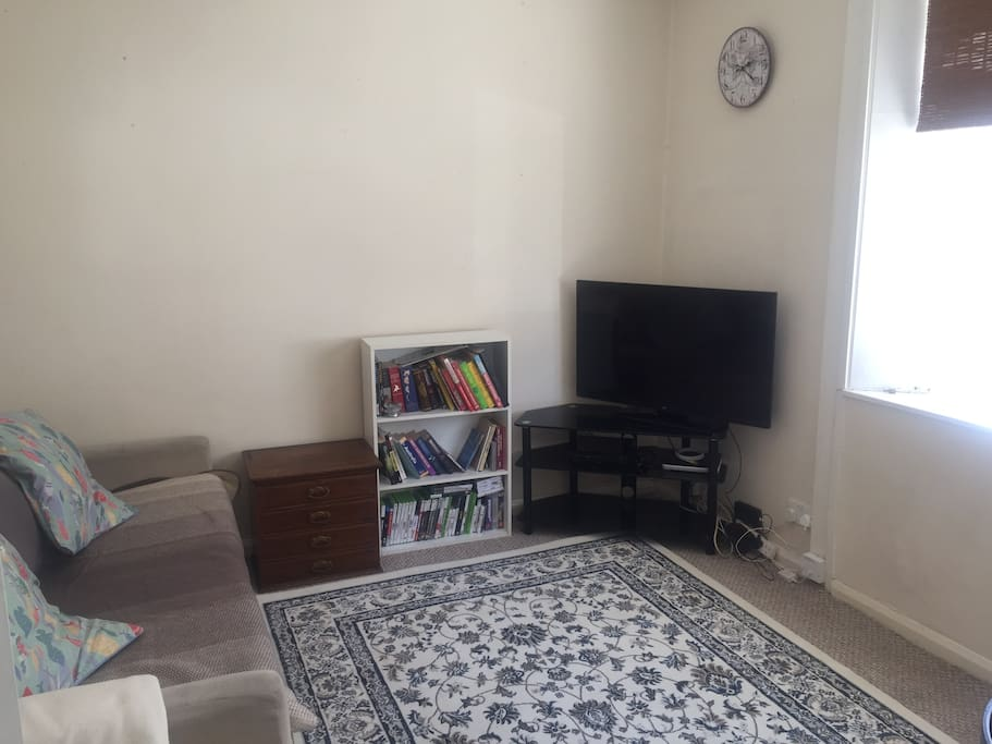 Lovely bright living room with sofa, dining table in the corner (shown in other pics), and a big bay window looking out onto the street. Sofa will be equipped with comfy bedding when a 5th person is staying and sofa pillows are easily rearranged for a comfortable stay.