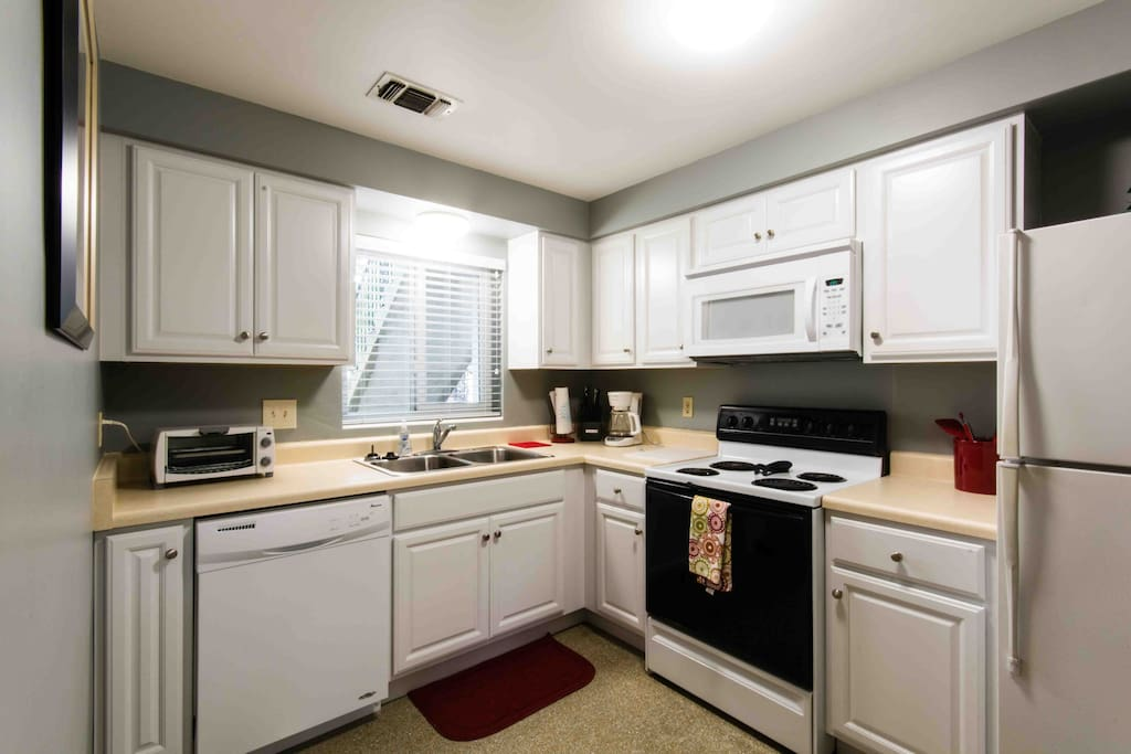 Kitchen with all white appliances, dishwasher, electric stove with microwave over the top. Window shows outside view.
