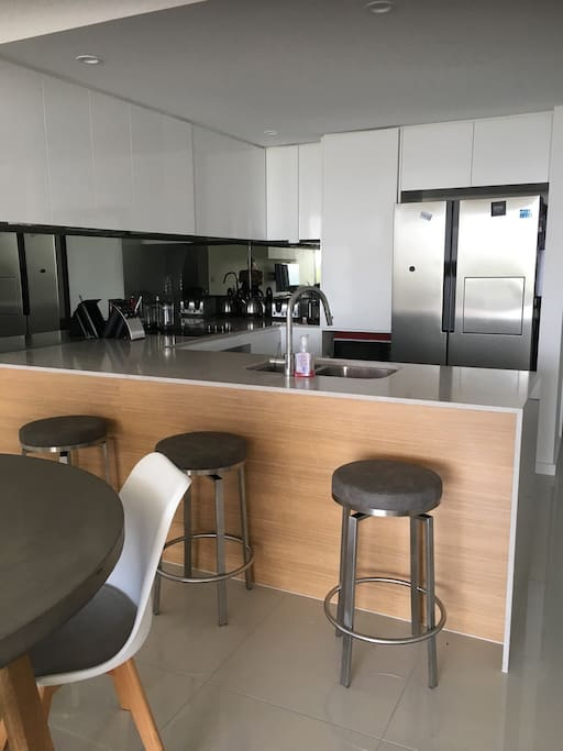 Kitchen with 'breakfast bar' seating...   Large fridge/ freezer combo. Includes dishwasher, toaster, kettle, Nespresso Machine and Nutri Bullet (necessities in life right?)
