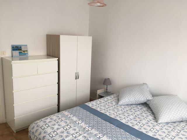 Chambre à coucher, lit queen size, commode et penderie, tables et lampes de chevet.