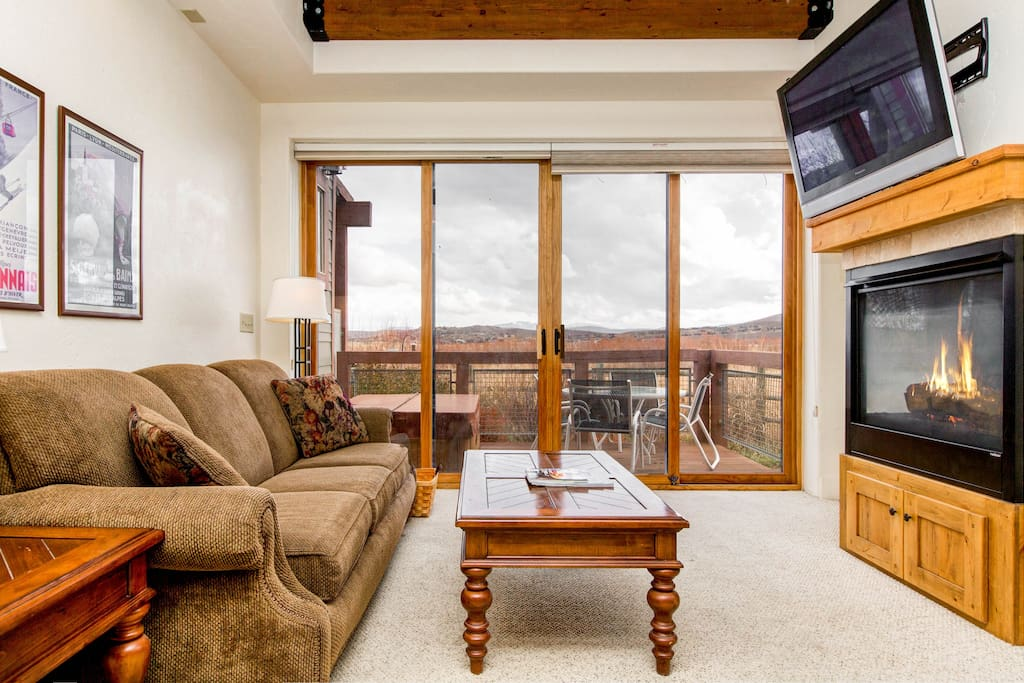 """A plush sofa sits in front of a gas fireplace and 42"""" flat screen TV in the living room."""