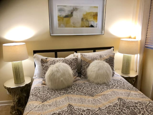 The apartment's inviting bedroom is not only ready for a great night's sleep, but features the artistic flare of a professional designer.