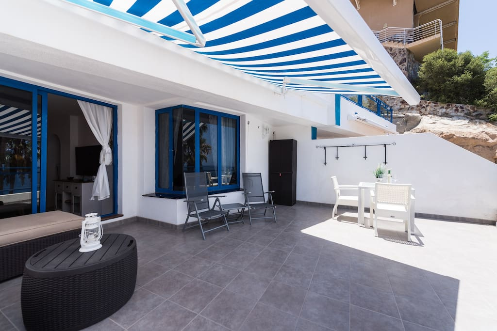 Large terrace with sofa group, sun beds and dining table.