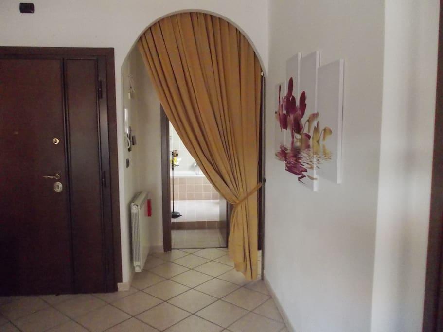 Porta d'ingresso e arco con tenda da cui si accede al bagno e alla camera da letto matrimoniale