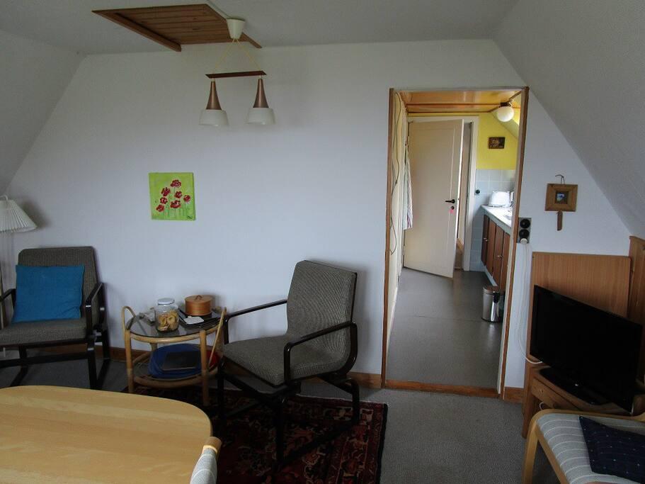Dette er stuen. Du ser ud i køkkenet og bag dig altanen med udsigt over Østersøen og mod Gudhjem