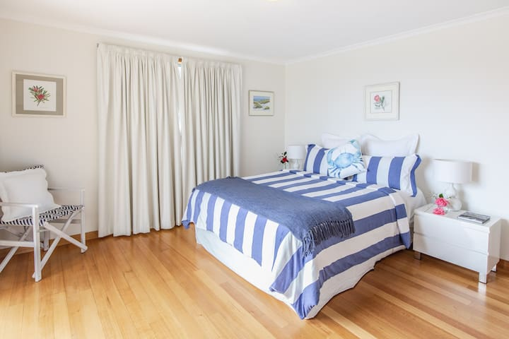 The generous sized master bedroom has an en-suite and glass sliding door onto the timber deck with stunning waterfront views