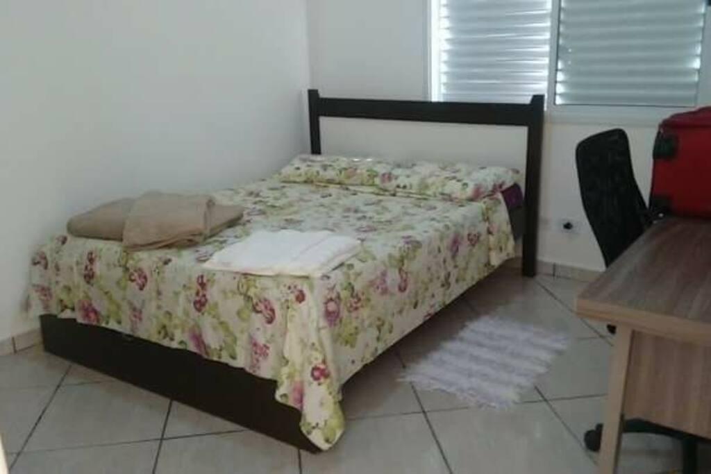 Cama de casal, nesse quarto tem uma escrivaninha e cadeira de escritório para trabalho estudos ou leitura