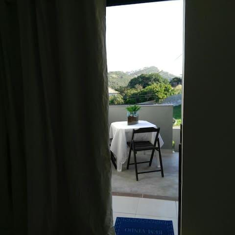 Foto tirada de dentro da sala/quarto. Ao fundo temos a varanda com a mesa e duas cadeiras e a direita a descida da escada.