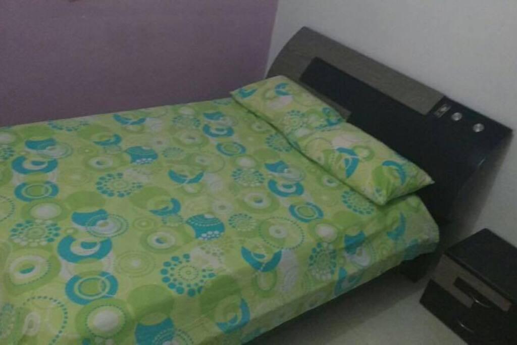 Habitación con cama doble y aire acondicionado.