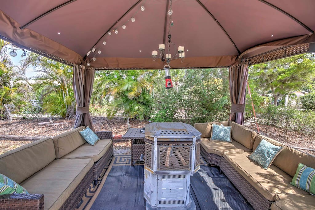 Enjoy gathering in the shade on the covered patio, complete with a fire pit and plenty of cushioned furnishings.