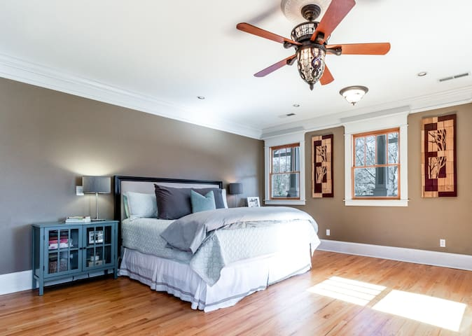 Welcome to the Master Bedroom! There are dual nightstands and lamps. And just look at that ceiling fan! We like to add flair and art anywhere!