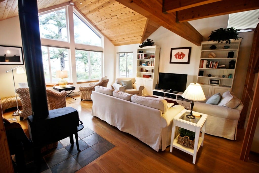Middle entry level living room with a flat screen cable TV/Blu-Ray DVD player, surround sound, wood stove, couch, 2 overstuffed chairs, 2 wicker chairs and large picture windows with ocean views