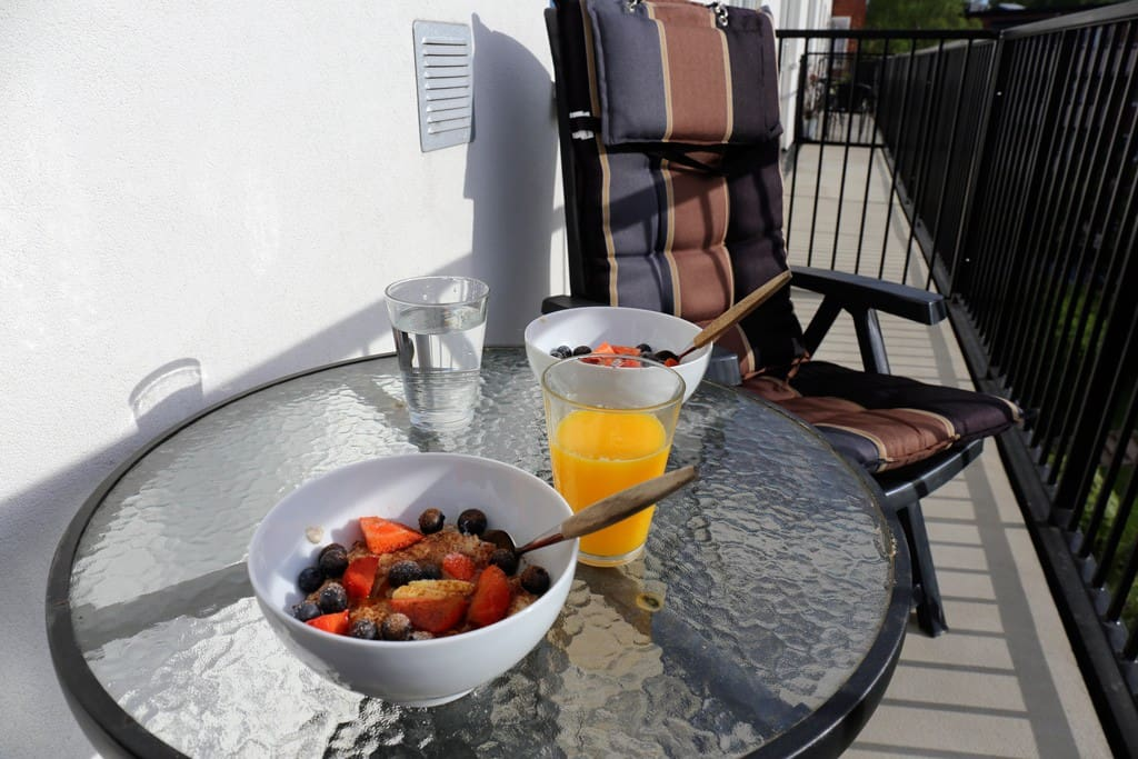 Enjoy breakfast on the sunny balcony, looking out towards a quiet backyard area.