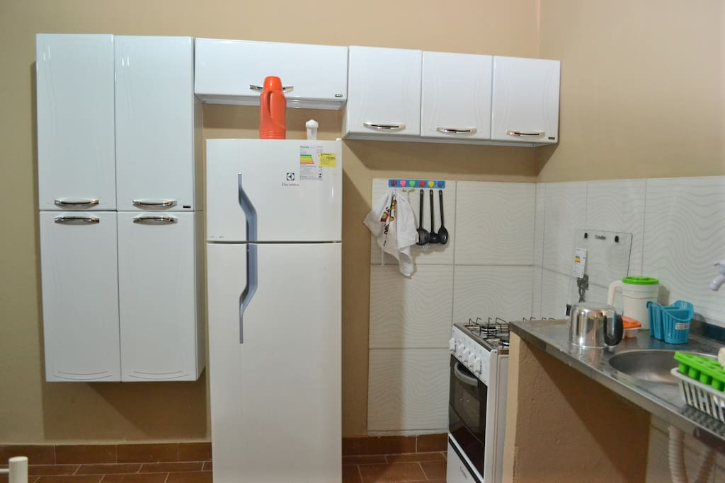 Cozinha com geladeira, fogão, armários, pia, e tudo mobiliado.