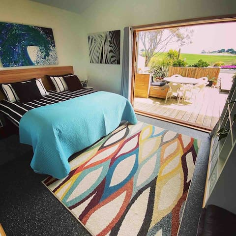 Beautiful master suite  with supremely comfy King sized bed, featuring double opening french doors onto a sun drenched private deck overlooking sweeping Hills to the West with a large flat screen tv
