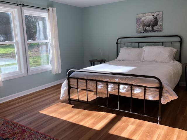 The master bedroom with a queen bed, decorated with a photo of one of our oldest sheep
