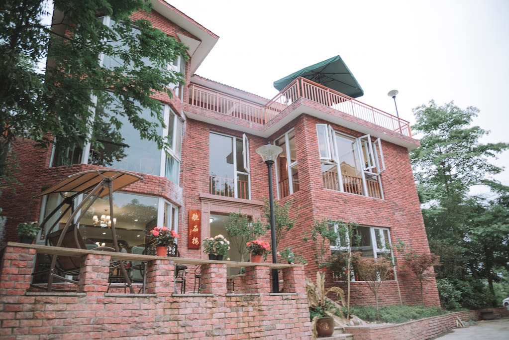 别墅外观,整栋别墅被郁郁葱葱的树林包裹,环境优雅宜人。
