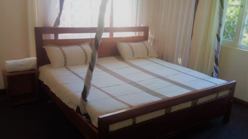 Spacious double room with king-sized bed, mosquito net and work space