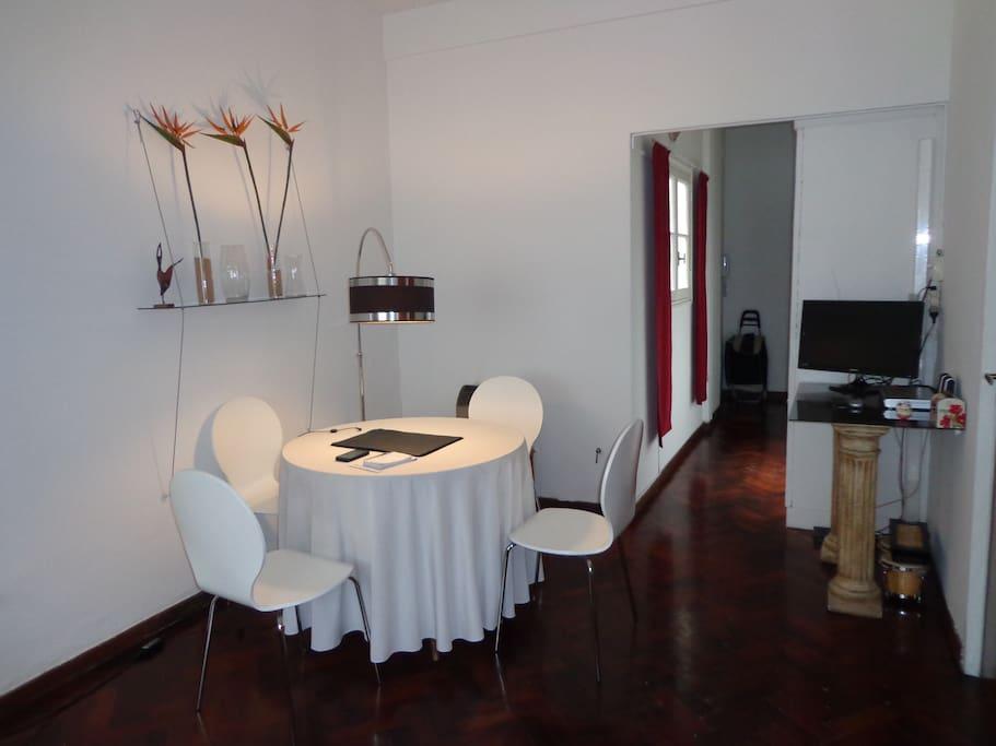 Mesa con cuatro sillas y una Lampara curva que le da mas calidez a la mesa ademas cuenta con un LED TV con servicio de cable