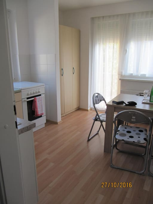 Kitchen with a kitchen table, cooking area (all utensiles and dishes are provided) and a fridge. There is an exit to the balcony