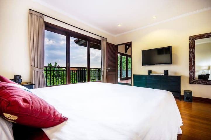 Upstairs bedroom with sliding doors for ocean breezes and natural lighting.