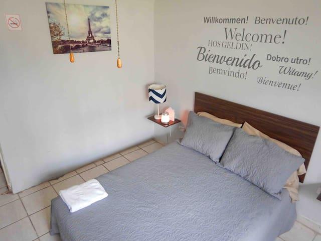 Habitación con cama matrimonial, contactos cercanos a la cama, repisas y lampara de noche. Sabanas, colcha y almohadas limpias el dia de tu llegada.