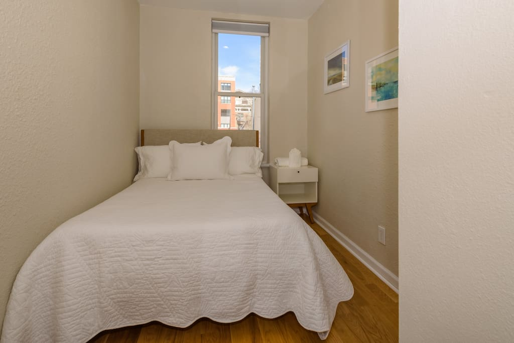 The cozy second bedroom has a double bed with a Leesa memory foam mattress, bedside table and city views.