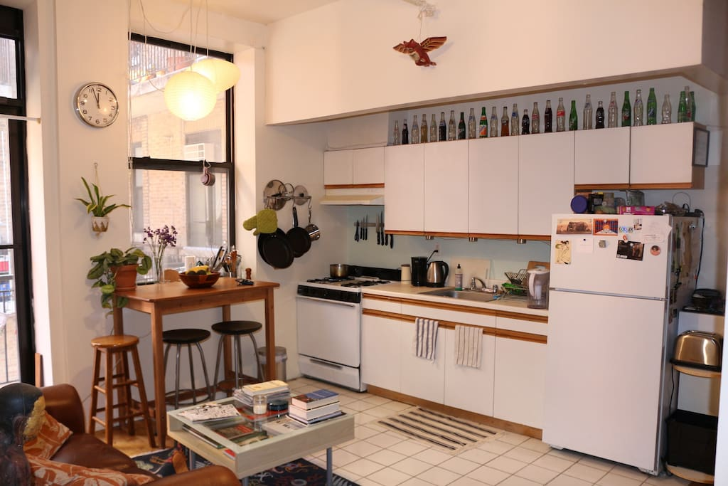 The bright and airy kitchen area is stocked with appliances and a high table perfect for meals and drinks.