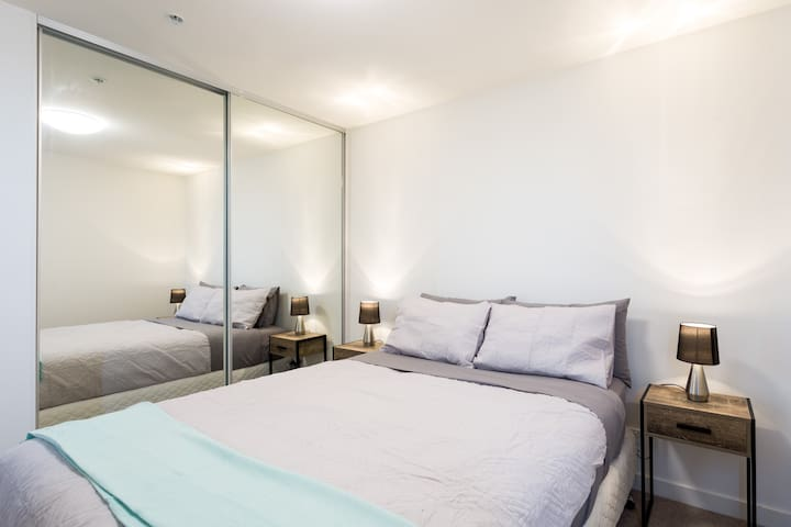 The second bedroom with queen bed and sliding mirrored robe offers a comfortable place to rest up after a long day