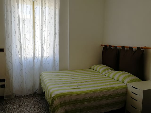 Room with double bed, kitchen and shared bathroom